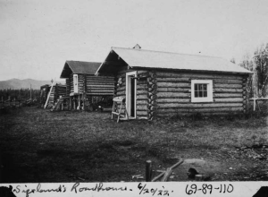 "Photo caption: ""Sizeland's Roadhouse, 6/20/'22."" Bottom left corner of this photo is torn off along with some writing. This photo is a side view of Sizeland's property shown in UAF-1969-89-108 and UAF-1969-89-109. Cabin closest to the camera has a sawhorse in front of the door. A cache with a painted door is located to the left of the cabin; a flat-roofed building sits to the left of the cache. [UAF-1969-89-110]"